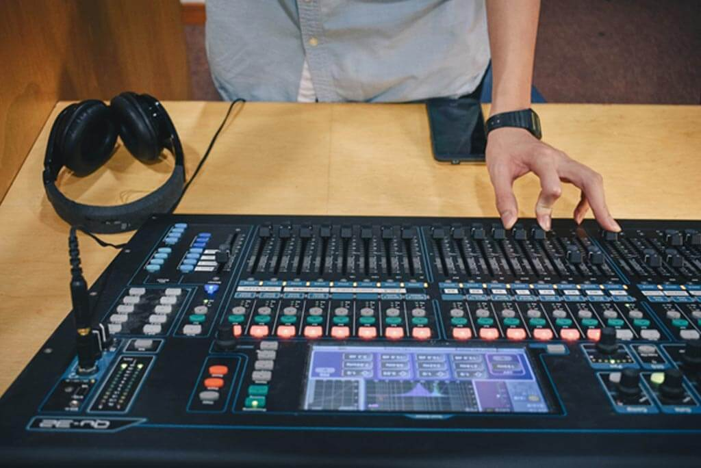 Man operating mixing console